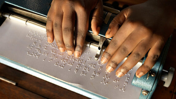 A close-up of a girl's hands as she reads from a braille document.