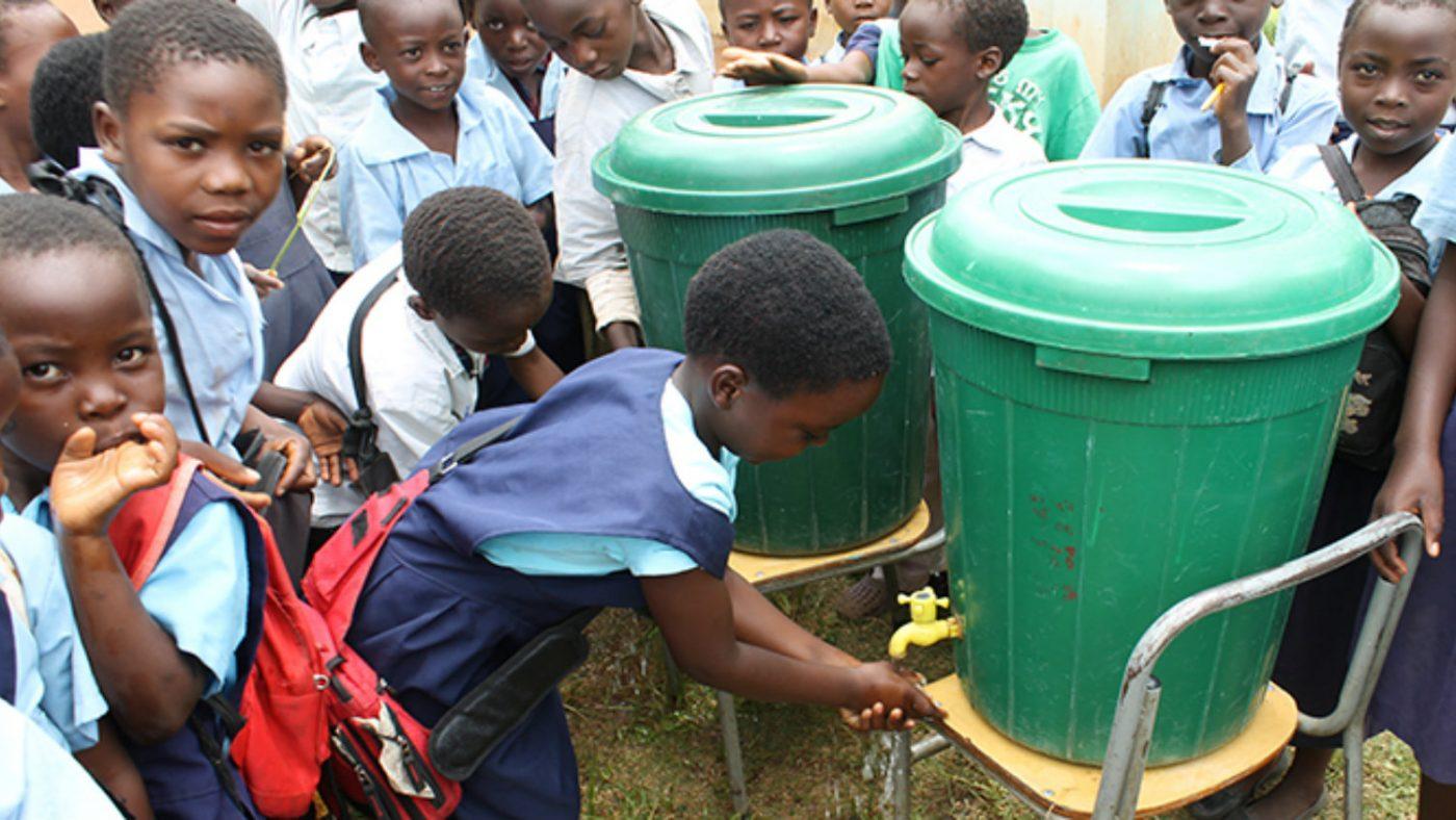 Barn vid grundskolan i Mwase tvättar sina händer.
