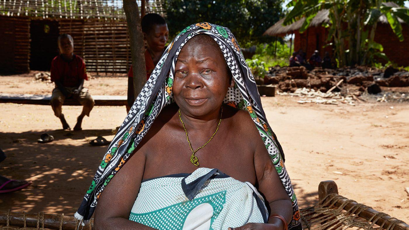 Agnes sitter utanför sitt hem i Tanzania.