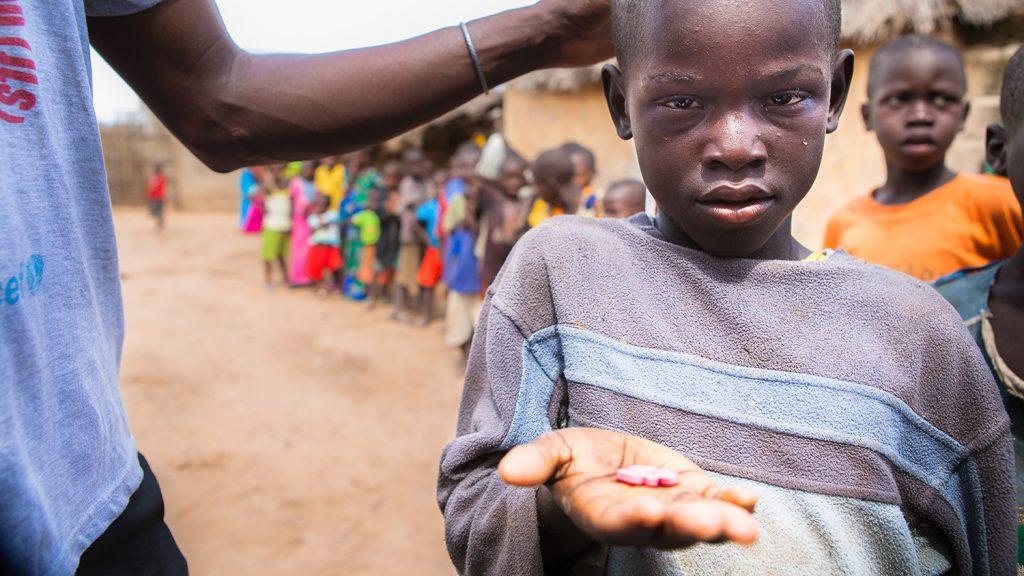 En ung pojke håller upp sin hand mot kameran och visar tabletterna han fått mot trakom.
