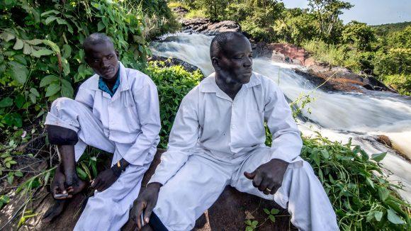 Två fältarbetare tar en paus bredvid floden Agogo i Uganda.