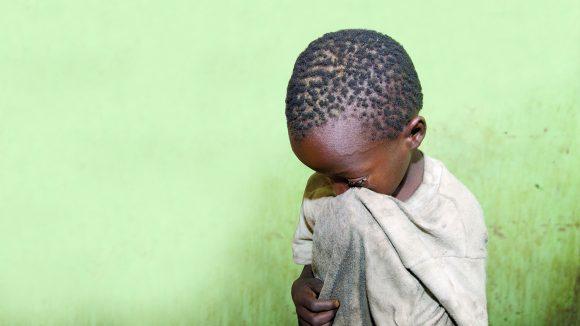 En ung pojke torkar ögonen med sin t-shirt.