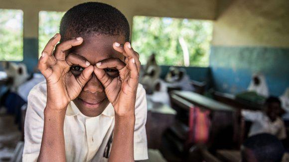 En pojke formar ett par glasögon med sina händer.