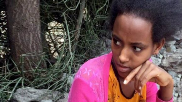 Rahel sits quietly outside her home.