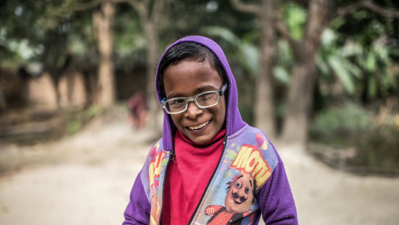Majidul, wearing glasses, smiles.