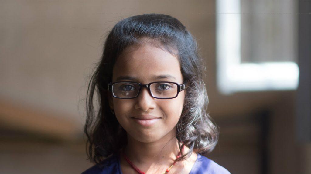 Riya, wearing her glasses, smiles.