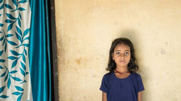 Riya, without glasses, stands against a wall.