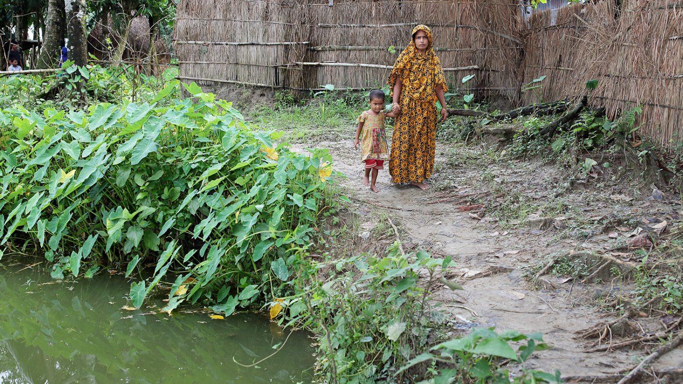 Aklima håller sin mammas hand när de går förbi en damm vid deras hem.