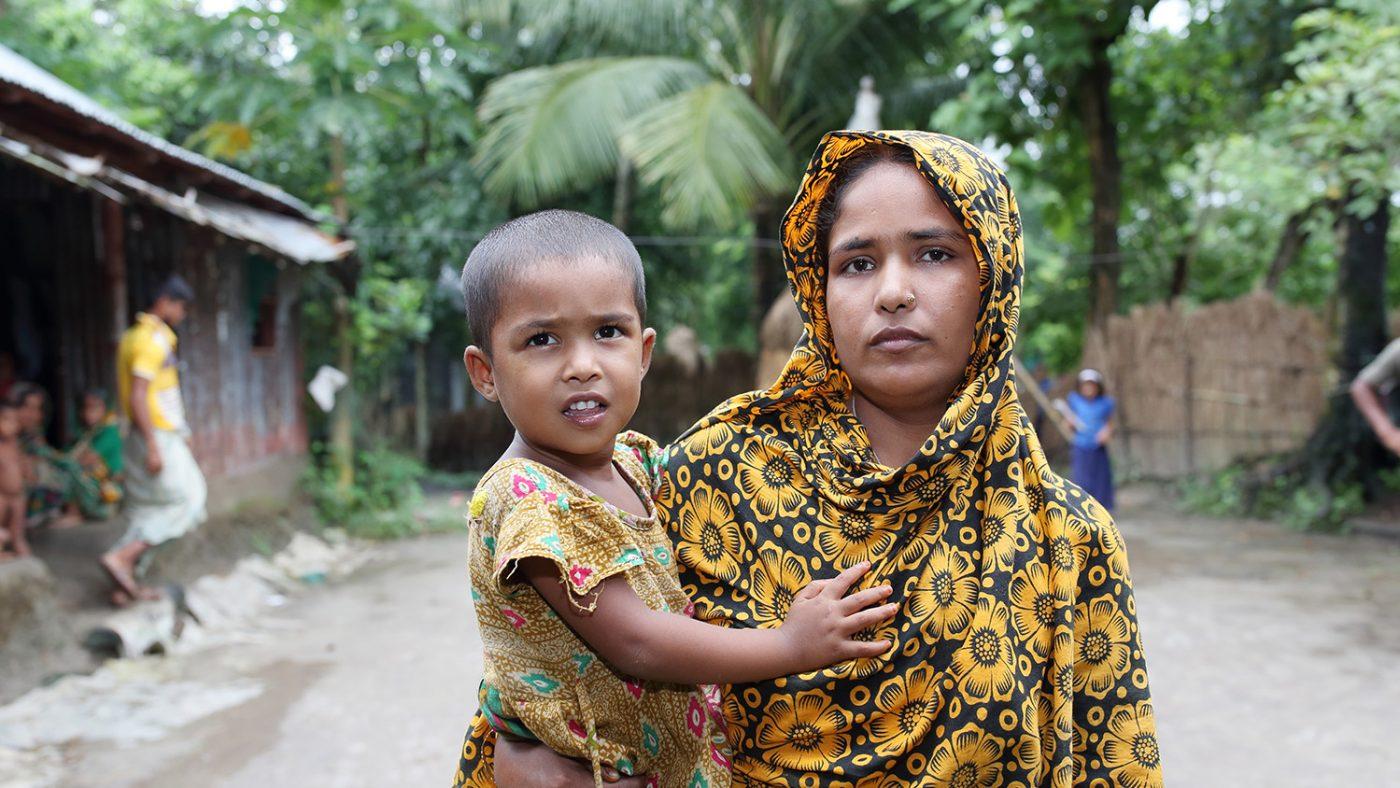 Aklimas mamma håller henne i sin famn.