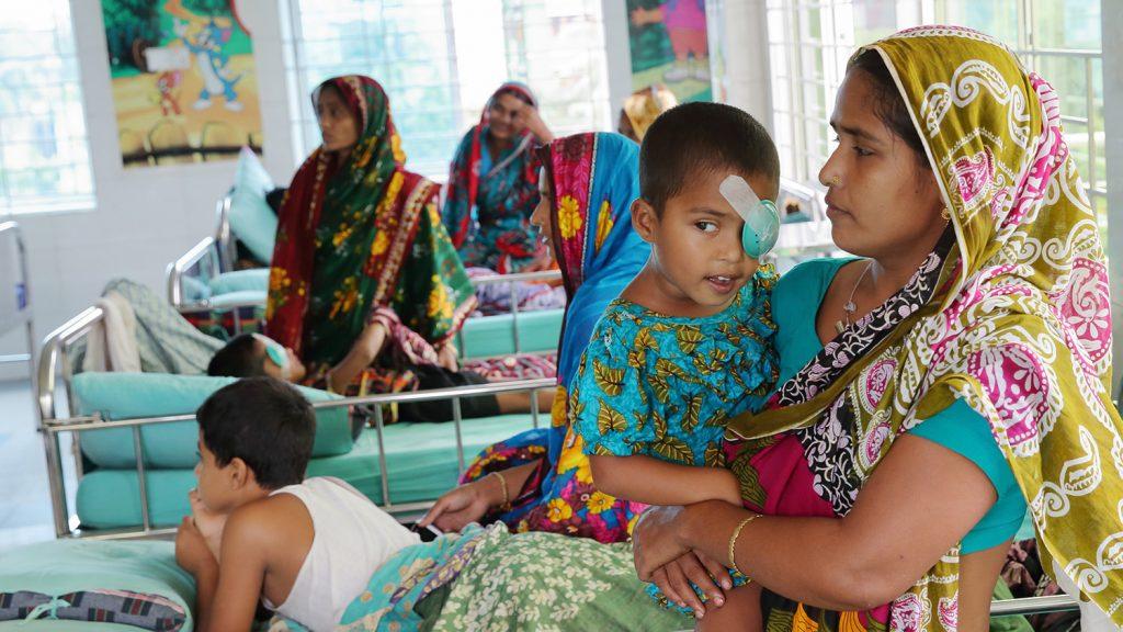 Aklimas mamma kramar om henne efter operationen. Hon har en grön plastkopp på ansiktet för att skydda sitt öga.