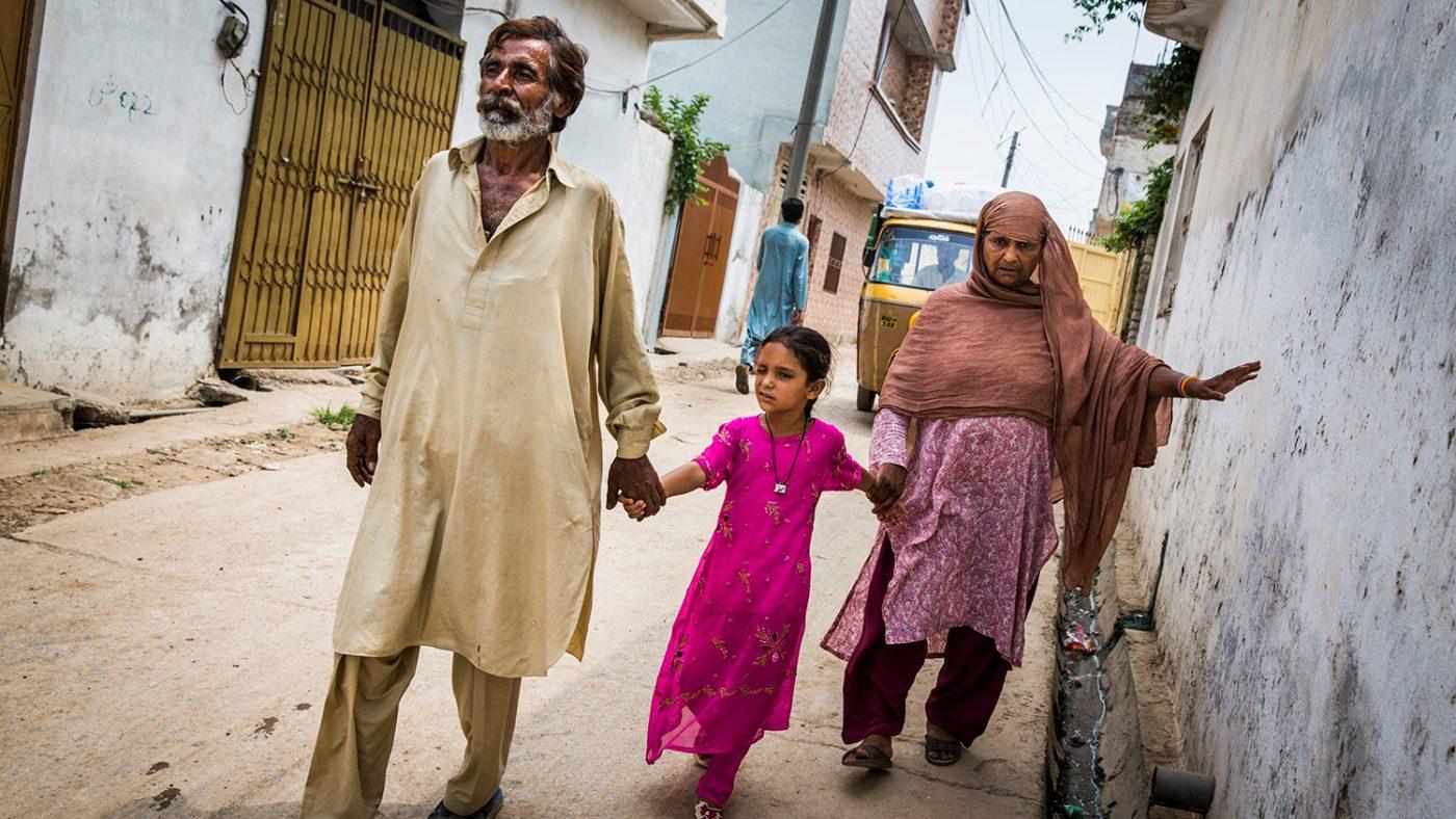 Zamurrad stöder sig mot en vägg med ena handen och leds av sin dotter med den andra.