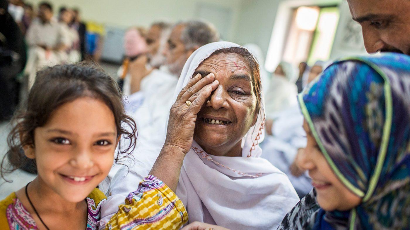 Zamurrad håller en hand mot ena ögat medan hon och hennes dotter ler mot kameran.