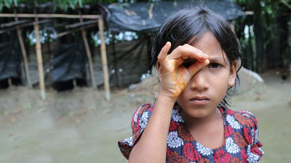 En ung flicka kupar handen för ena ögat i ett försök att skärpa synen.