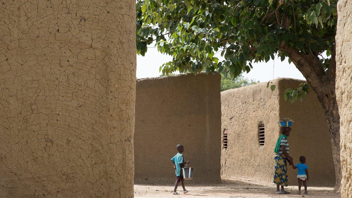 Människor går mellan två lerhus i den maliska byn där Sayon bor.