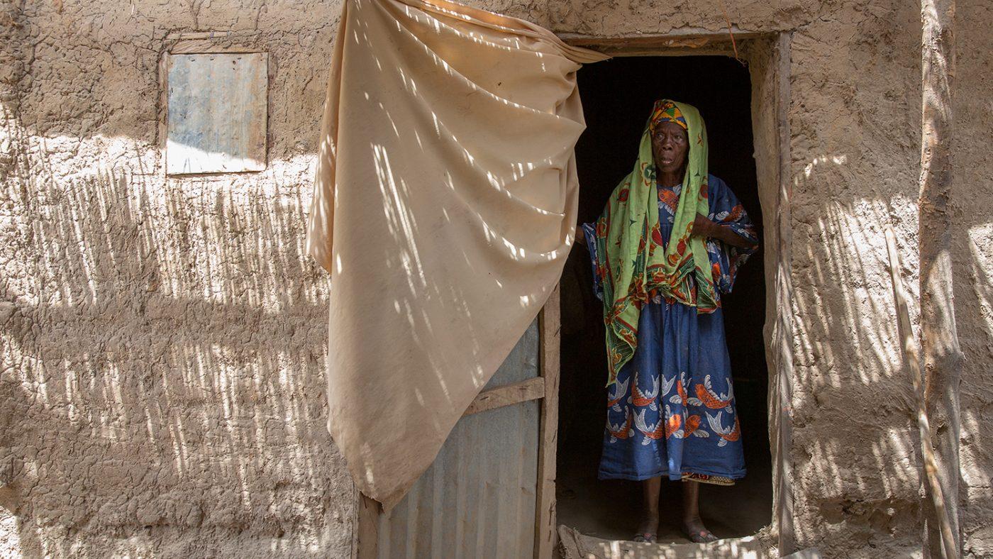 Sayon står i dörröppningen till sitt hus. Hon bär en lång, blå klänning och en sjal över huvudet.