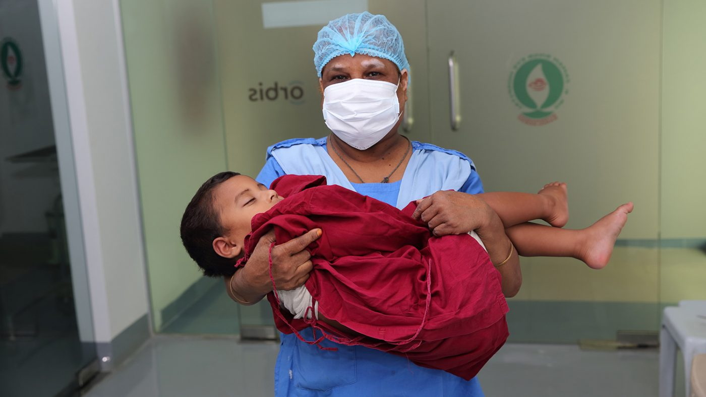 Nadir bärs in i operationssalen av en sköterska.