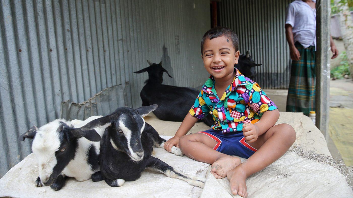 Nadir sitter bredvid familjens getter och ler.