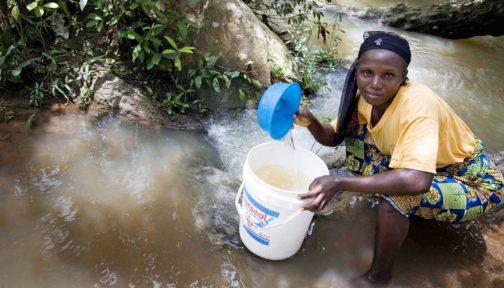 En kvinna sitter på huk i en å och samlar vatten med en hink i Nigeria.