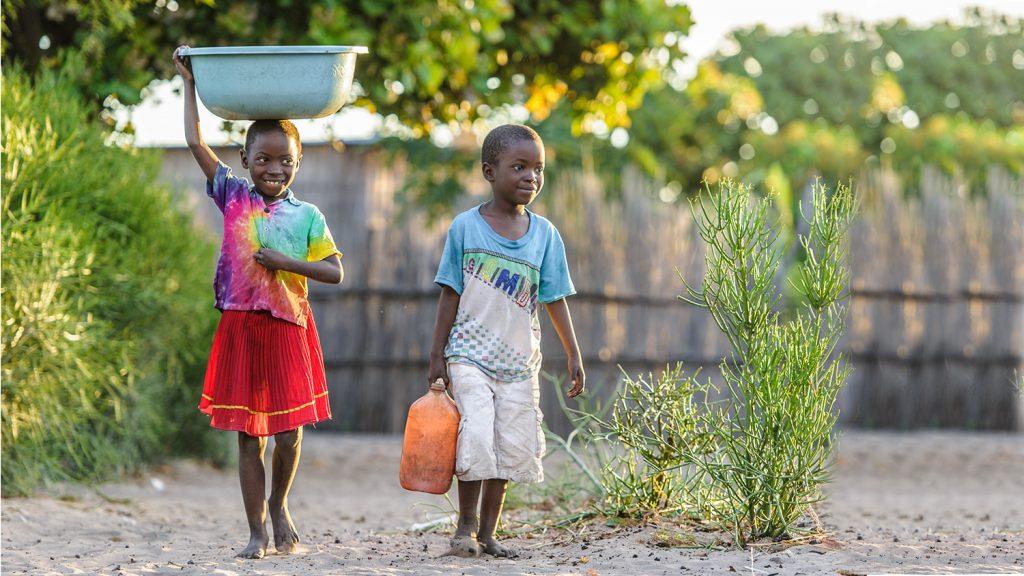 Namukolo och hennes bror bär vattenhinkar genom byn där de bor.