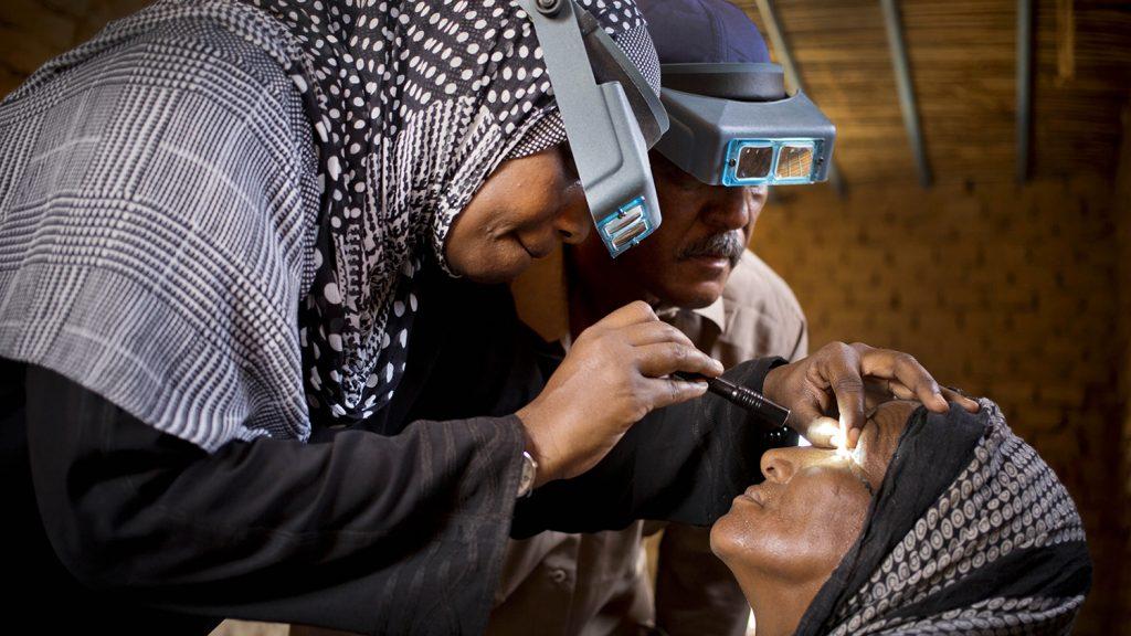 En sjukvårdare undersöker en kvinnas ögon för att leta efter tecken på trakom.