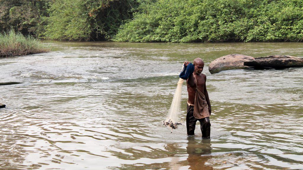 Emmanuel fiskar i Prufloden. Han står i knädjupt vatten och håller ett fiskenät i handen.