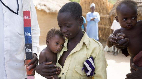 En liten pojke och hans lillebror väntar på att få medicin mot försummade tropiska sjukdomar i Nigeria.