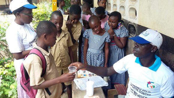 En grupp byinvånare står i kö för att få sin medicin av en CDD-volontär. Han ger den till dem i en plastmugg.