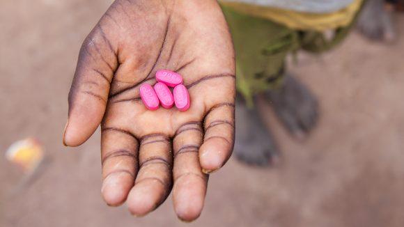 Ett barn i Senegal håller fyra Zithromaxtabletter i handen.