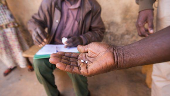 En man med läkemedel mot försummade tropiska sjukdomar i handen.