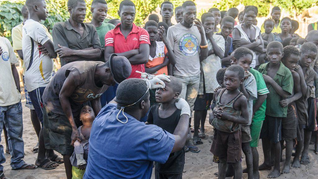 Mr Ndalela står på ett knä och undersöker ögonen på barn som står på kö.
