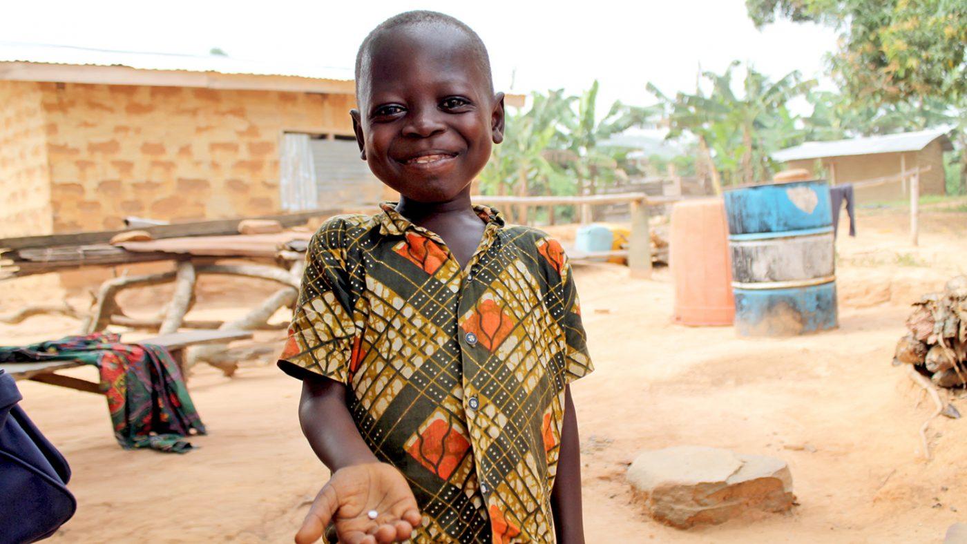 En pojke håller en tablett som används för att behandla försummade tropiska sjukdomar.