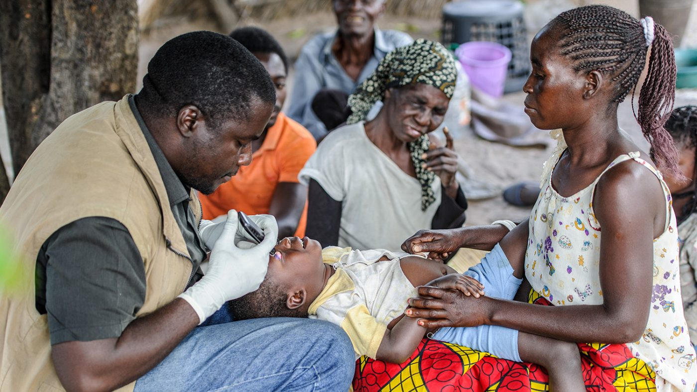 En mamma hjälper Mr Ndalela att hålla barnet så att han kan undersöka ögonen.