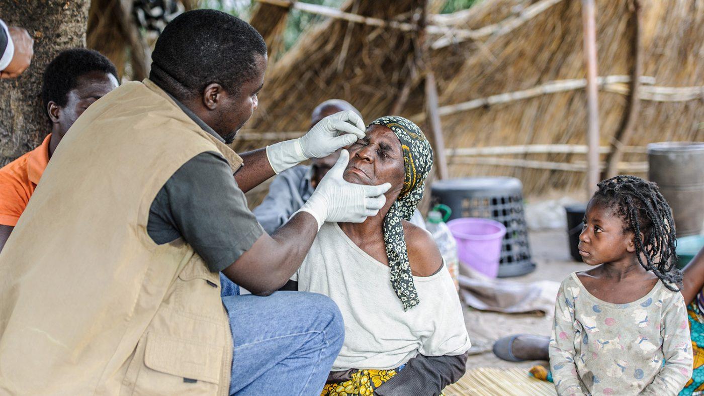 Mr Ndalela undersöker en äldre kvinnas ögon för att leta efter tecken på trakom.