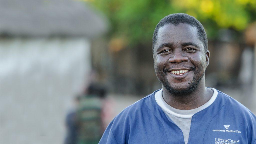 Mr Ndalela står i sina kirurgkläder och ler brett in i kameran.