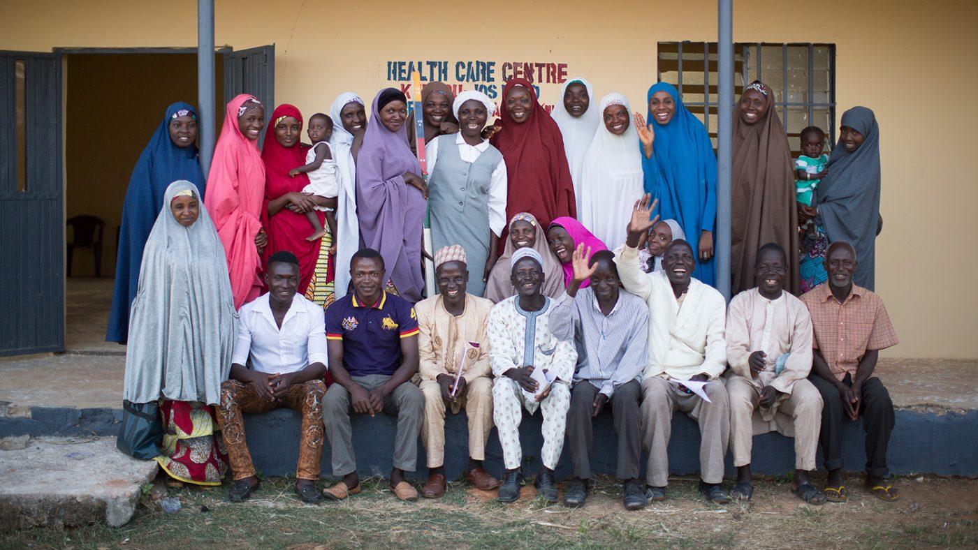 En grupp CDD-volontärer i Nigeria står utanför byggnaden där de får sin utbildning.