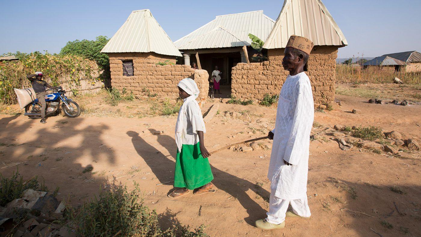 Dorcas leder sin farfar genom byn.