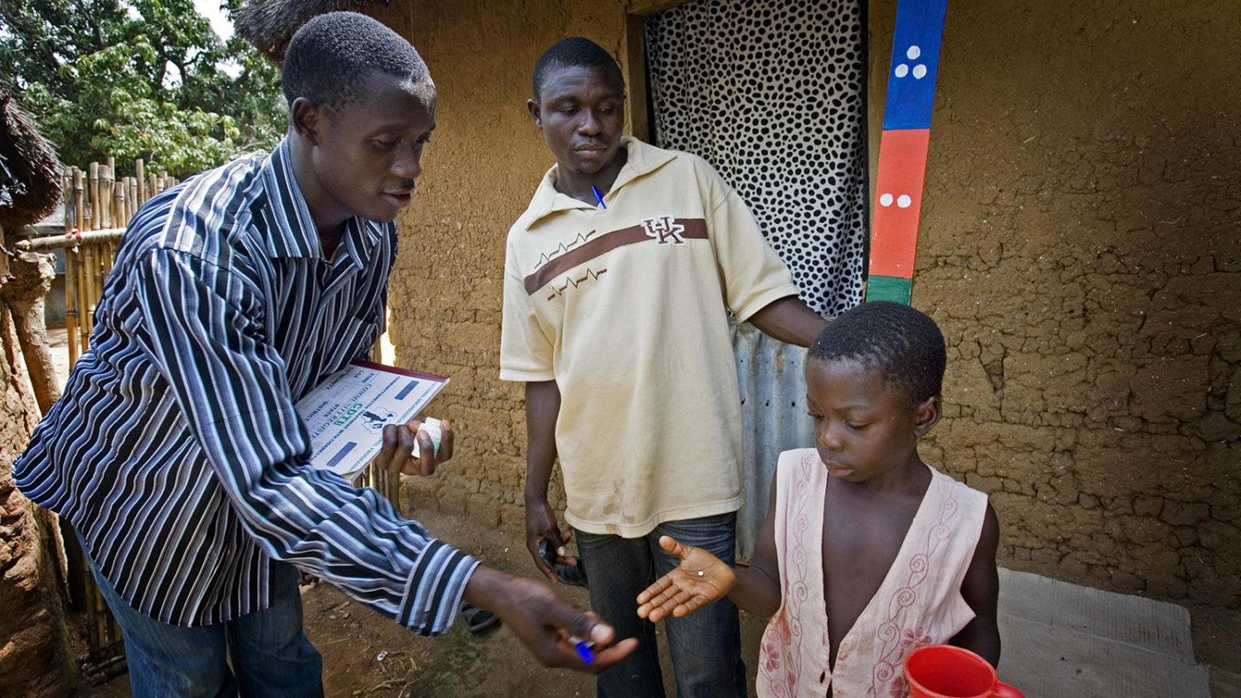 En lokal volontär delar ut läkemedel som skyddar mot flodblindhet och lymfatisk filariasis.