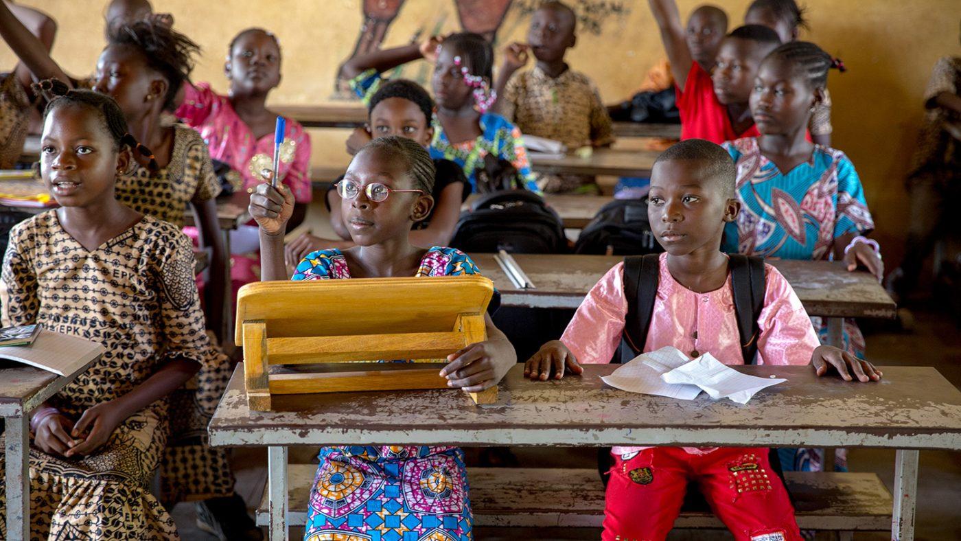 Mafoune räcker upp handen för att svara på en fråga i skolan.