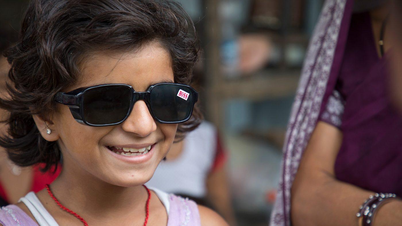 Muskan sitter leende hemma med mörka solglasögon.