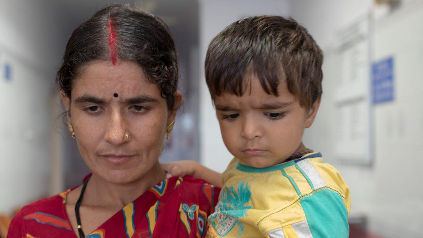 Chandrakala håller sin yngsta son i famnen. Han har också grå starr.