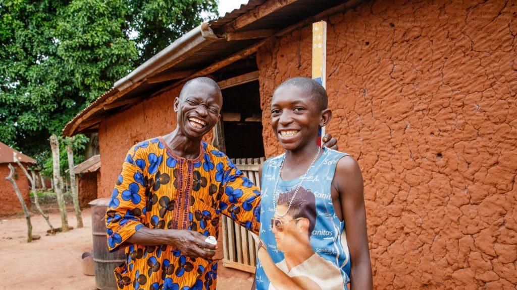 Två män skrattar och ler. Den ena mäter den andra med en doseringsstav.