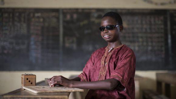 En ung pojke läser blindskrift i ett klassrum.