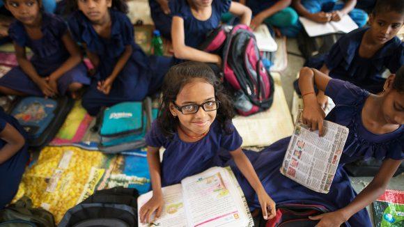 Riya sitter med en bok i knät tillsammans med sina klasskamrater.