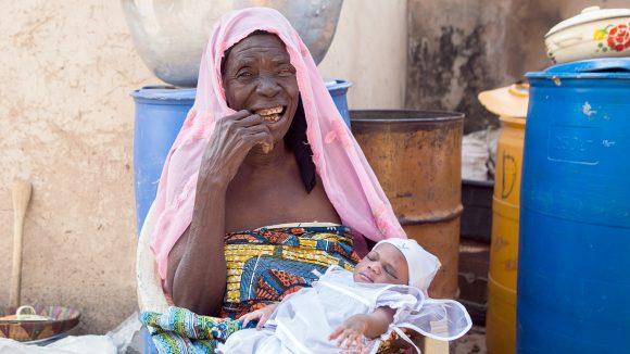En äldre kvinna sitter med ett litet barn i knät.