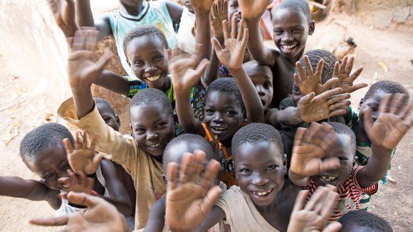 En grupp barn i Ghana som ler och vinkar åt kameran.