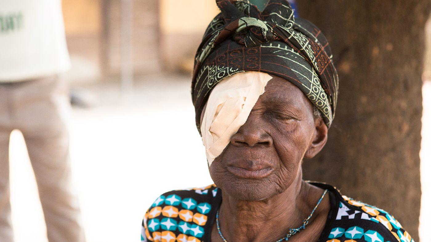 Ayishetu från Ghana sitter vid ett träd. Hon har ett förband över högra ögat efter att ha genomgått en trakomoperation.