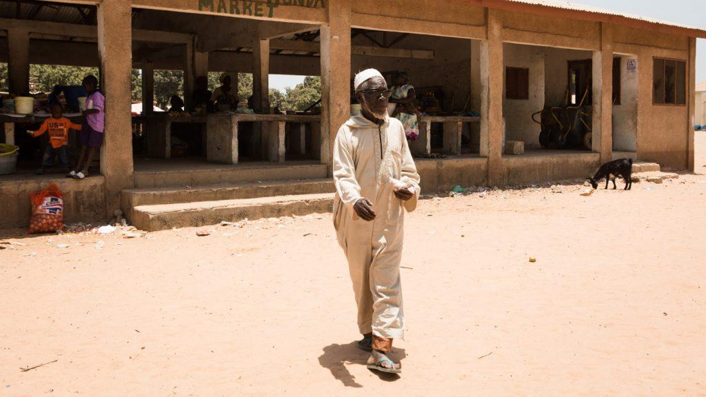 Yaya Manneh vandrar genom sin by.