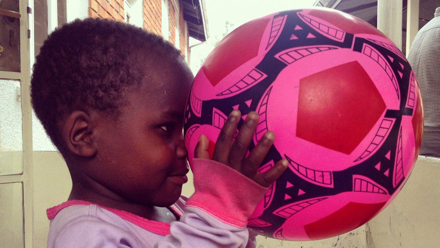 Criscent håller upp en rosa fotboll framför ögonen och tittar på den.