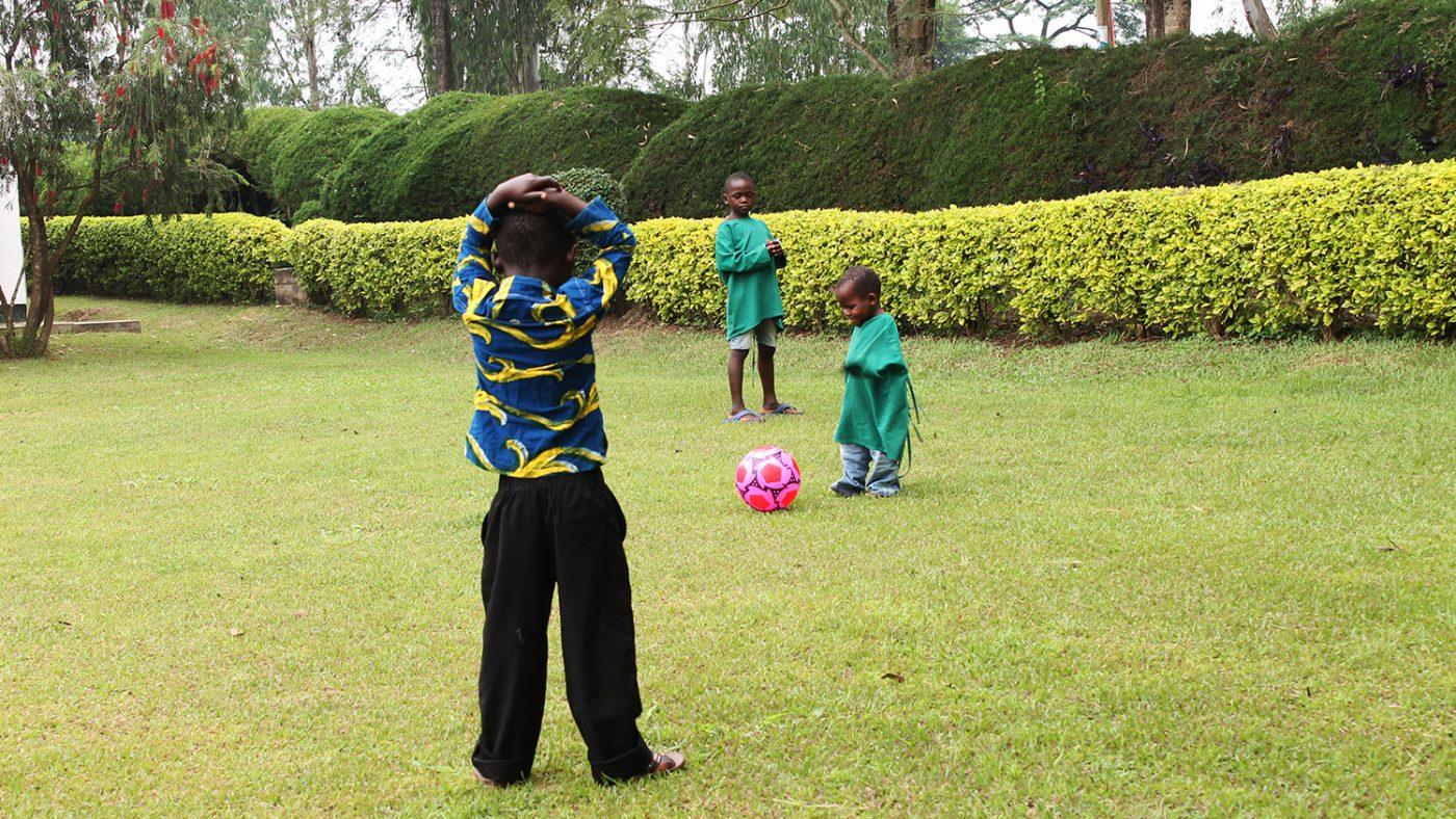 Criscent springer efter en rosa fotboll under en fotbollsmatch på sjukhusets gräsmatta.