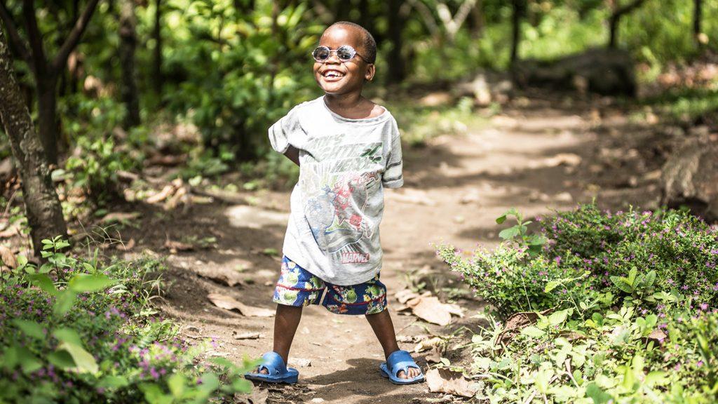 Criscent står i skogsbrynet nära sin hemby och ler brett mot kameran.
